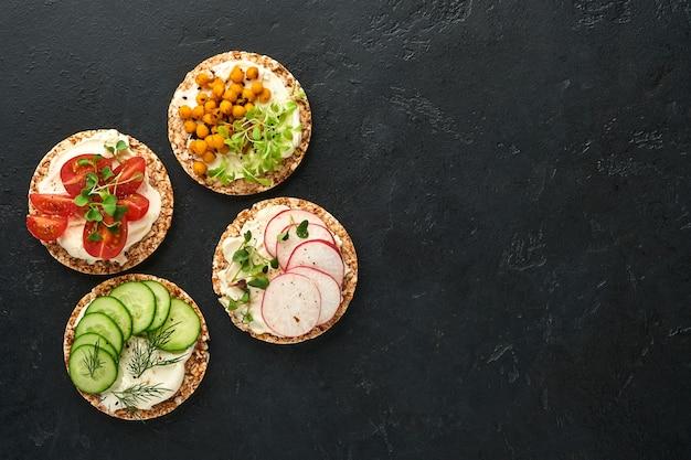크림 치즈, 무, 토마토, 병아리콩, 오이, 마이크로그린을 곁들인 바삭한 메밀 빵 4개는 검은 돌 배경의 양피지에 건강한 아침 식사를 제공합니다. 채식주의자와 건강한 식생활 개념.