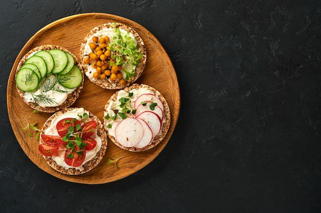 Four crispy buckwheat bread with cream cheese, radish, tomato, chickpea, cucumber and microgreen for healthy breakfast on parchment paper on black stone background. concept vegan and healthy eating.
