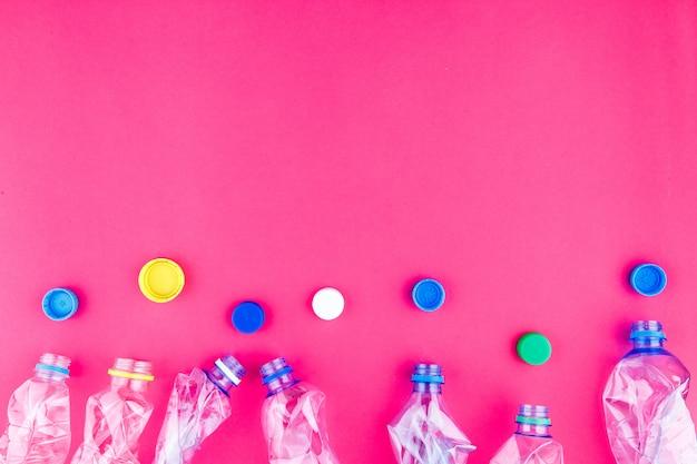 4つの砕いたペットボトルと鮮やかなピンクの紫色の背景にカラフルなキャップのクローズアップ。空きスペース。プラスチックコレクションのファッションの魅力的なコンセプト。生態学的なポスターテンプレート。
