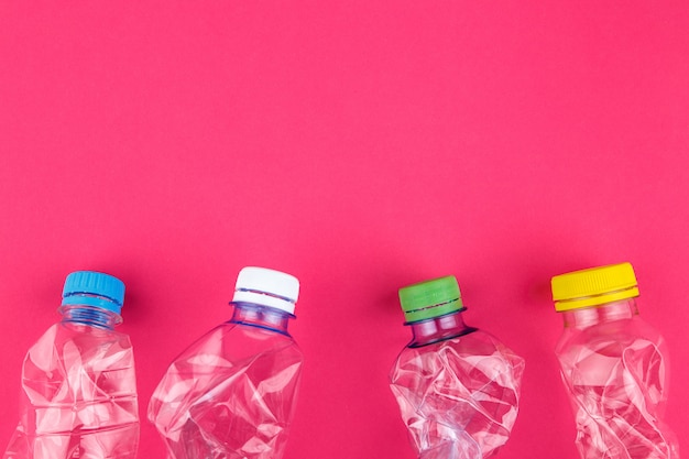 Four crushed pet bottles and colorful caps closeup on vivid pink background with room for text
