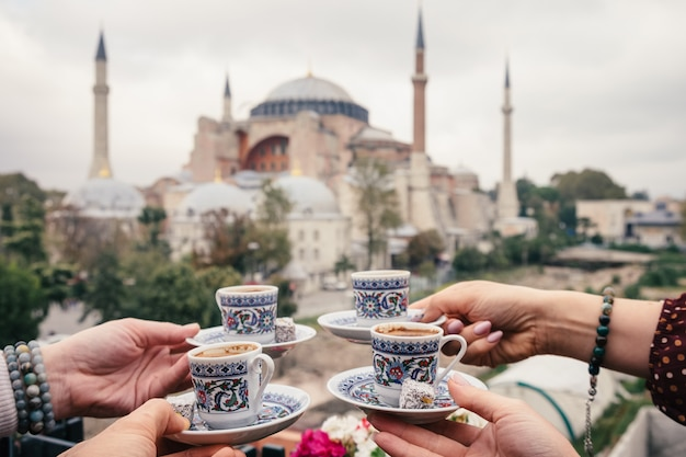 Four cups of turkish coffee in people hand on hagia sophia background, istanbul