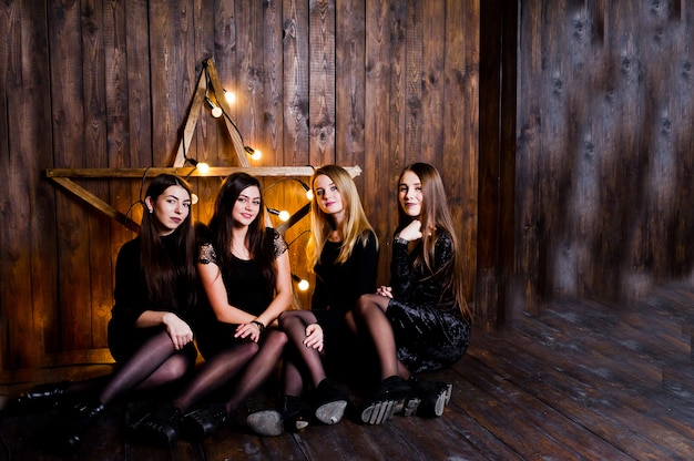 Four cute friends girls wear black dresses against large light christmas star decoration on wood wall