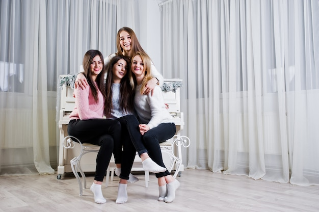 Four cute friends girls wear on warm sweaters and black pants against old piano with christmas decoration at white room.