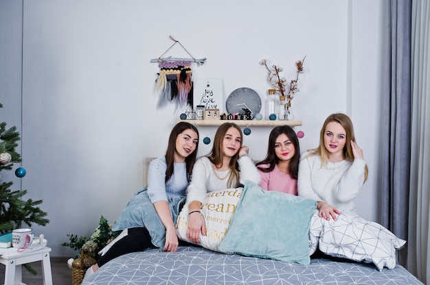 Four cute friends girls wear on warm sweaters and black pants on bed at decorated room on studio, play with pillows.