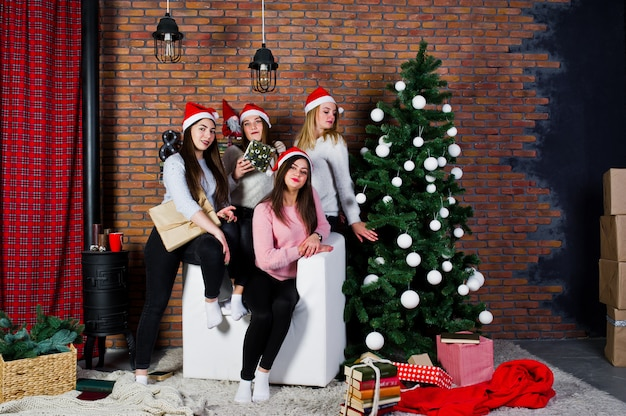 Four cute friends girls wear on warm sweaters, black pants and santa hats against tree with christmas decoration at studio.