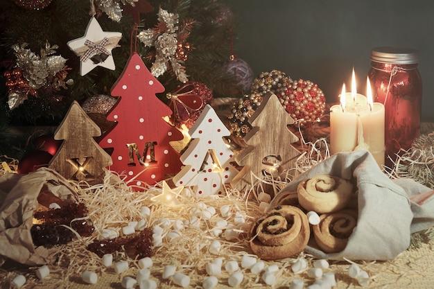刻まれた文字のクリスマスとクリスマスのお菓子と4つの装飾的な木製のクリスマスツリー。