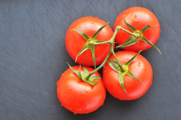Four delicious red tomatoes with water drops on the gray surface