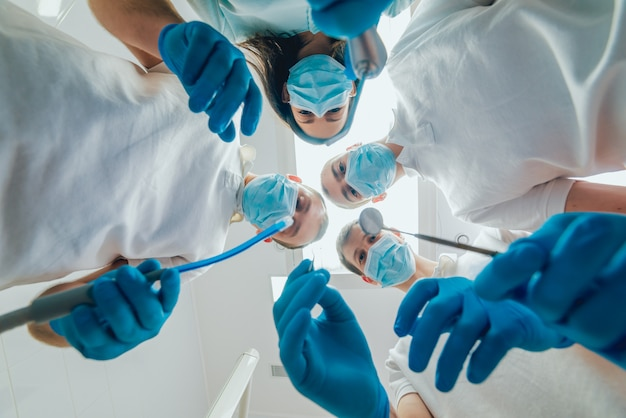 Four dentist in uniform perform dental implantation operation on a patient at dentistry office