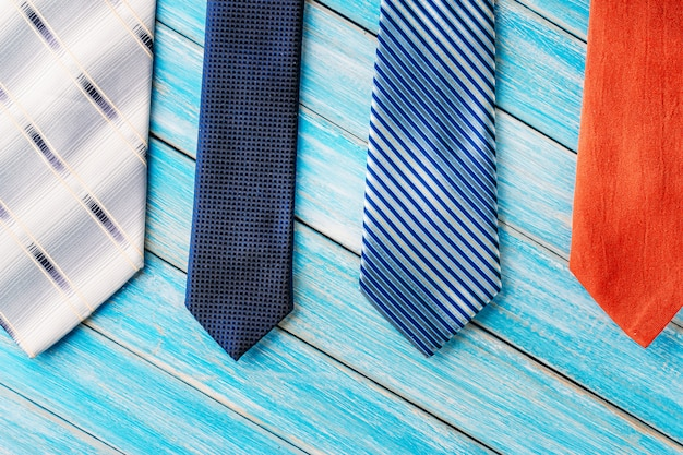 Four different colored ties in row on wooden blue background