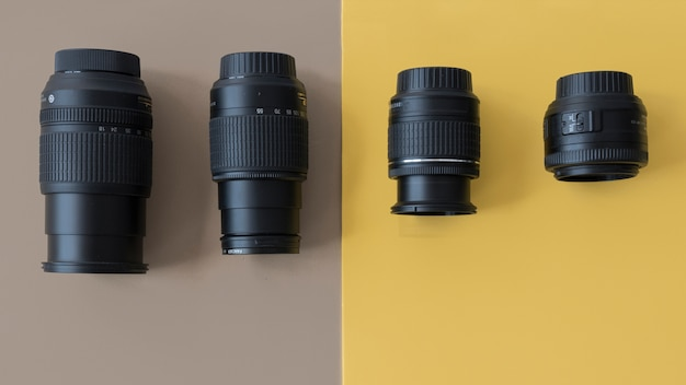 Four different professional camera lenses on dual background