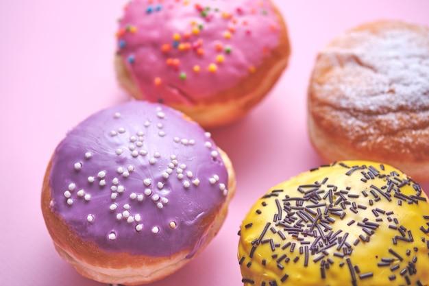 Четыре пончика с цветной глазурью на розовом бумажном фоне.