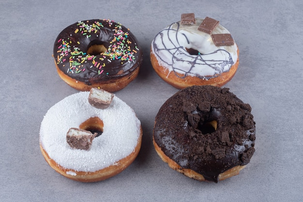 Four donuts with various toppings on marble surface