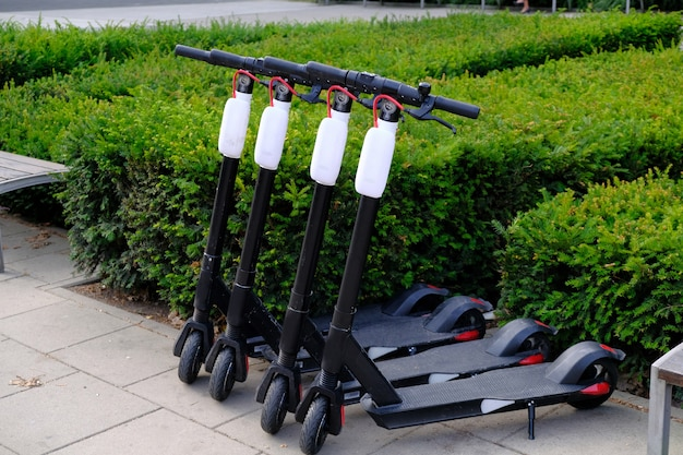 Four electric scooters parked in a row on city sidewalk.