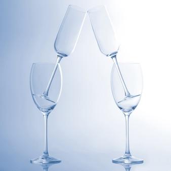 水色の背景に4つの空のワイングラス。飲用器具