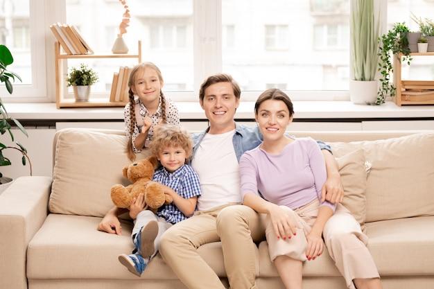 窓際のソファに座っているカジュアルウェアの家族4人
