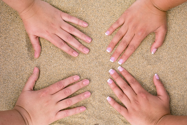 Four female hands placed on the beach sand.