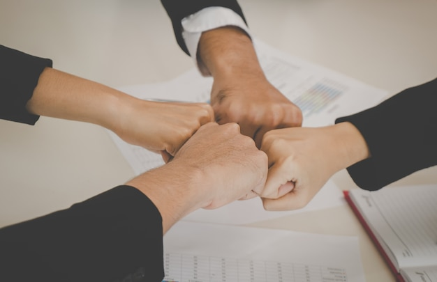 Four fist bump in business meeting for team concept