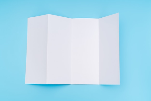 青い背景に4つ折りの白いテンプレート紙。