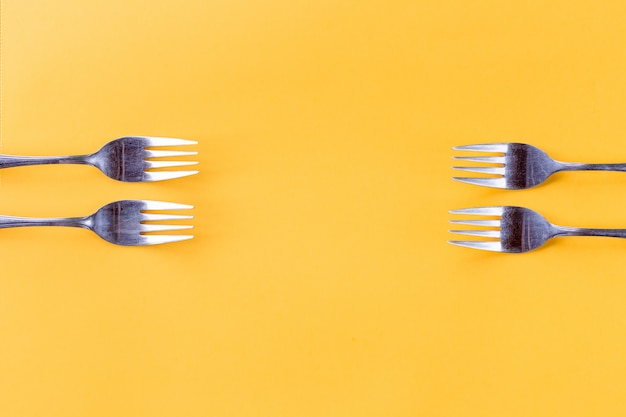 Four forks on yellow background