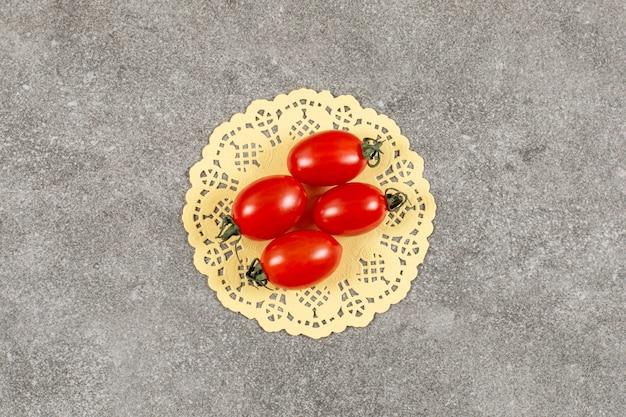 Quattro pomodorini freschi su grigio.