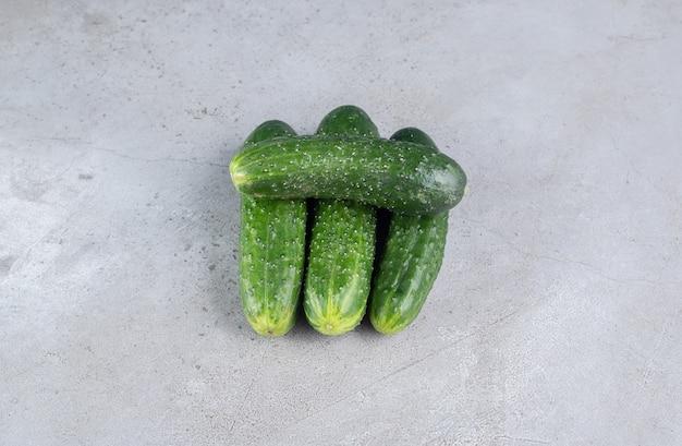 Quattro cetrioli freschi isolati su uno sfondo grigio. foto di alta qualità
