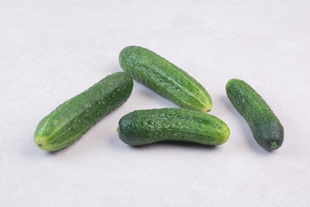 Four fresh cucumbers on white surface
