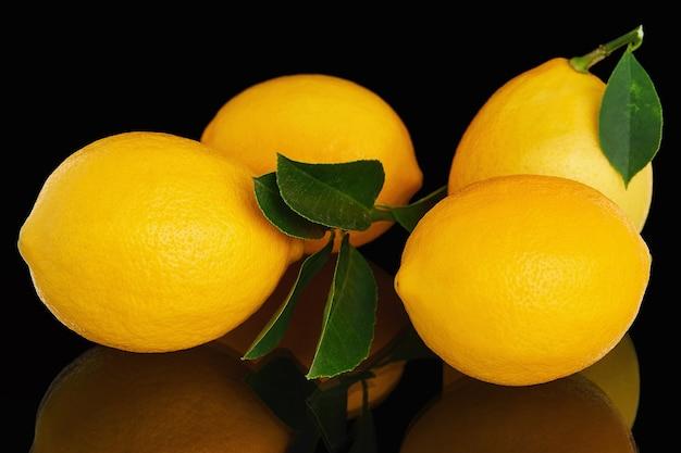 Four fresh ripe yellow lemons on black background