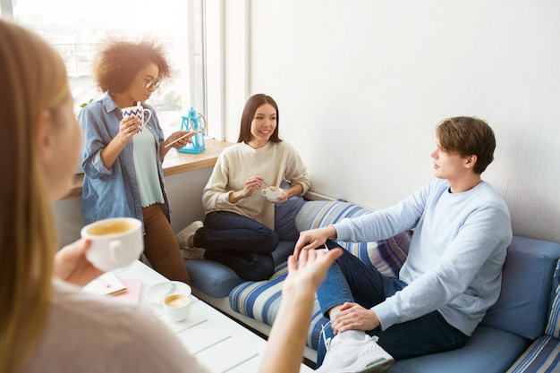 Four friends are gathered together. they are talking with each other and having some fun.