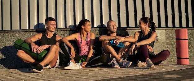 Четверо друзей-спортсменов сидят и общаются друг с другом