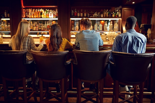 Four friends drinks beer at the counter in bar, back view. group of people relax in pub, night lifestyle, friendship, event celebration