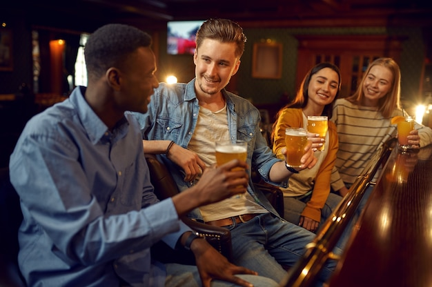 Four friends drinks beer at the counter in bar. group of people relax in pub, night lifestyle, friendship, event celebration