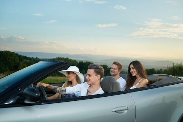Four friends going for drive, sitting in silver cabriolet.
