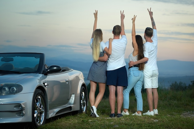 Four friends holding hands up, showing peace and admiring amazing view.