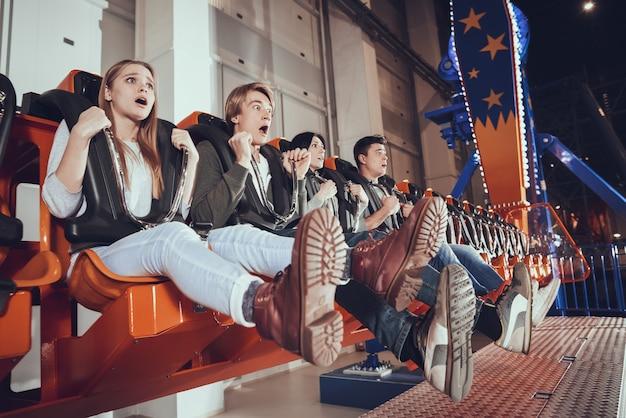 Four friends in shock at amusement park.