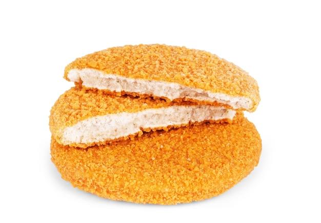 白い背景で隔離のパンでパンを焼いた4つの冷凍チキンカツレツ
