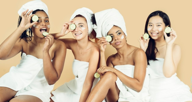 Four girlfriends relaxing with facial masks beauty creams