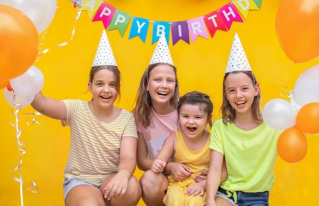 黄色の背景にボールを持つ4人の女の子。パーティーの子供たち