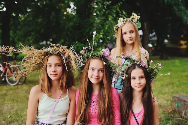 Four girls in wreaths of their wild flowers against the background of nature