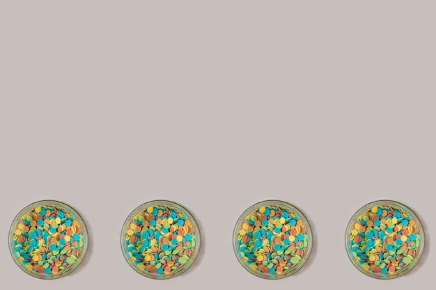 Four glass bowls with colorful candy sugar sprinkles on a pastel purple and gray background. minimal celebration wallpaper backdrop.