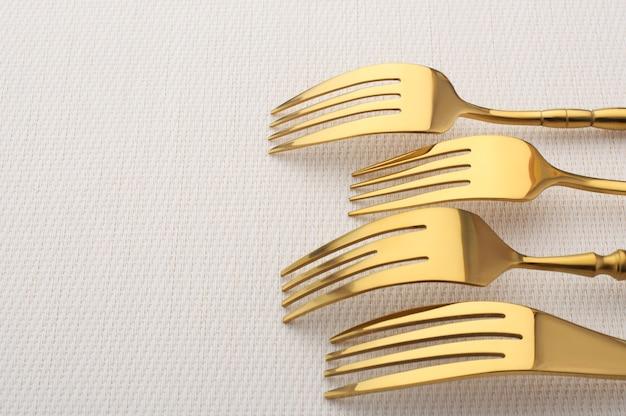 Four gold forks on a light pink tablecloth, golden flatwaer