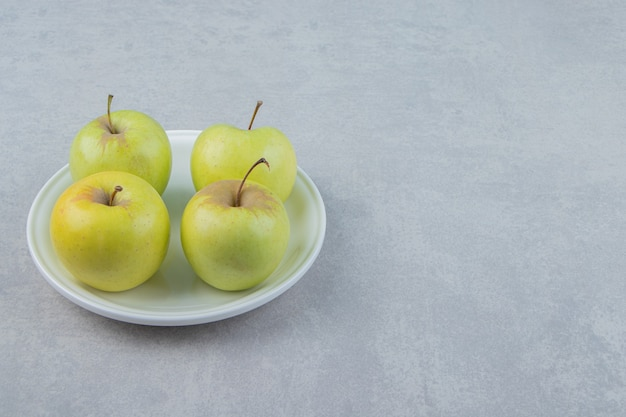 Four green apples on white plate