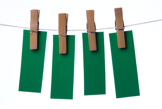 Четыре зеленых листа прикрепляют к веревке для белья на белом фоне