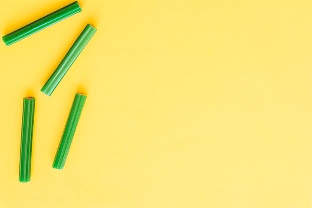 Four green soft licorice candies on yellow background