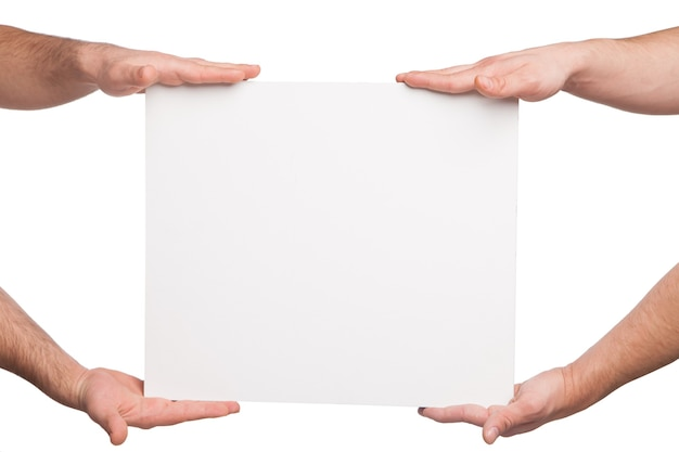 Four hands holding a blank white board. isolated on white