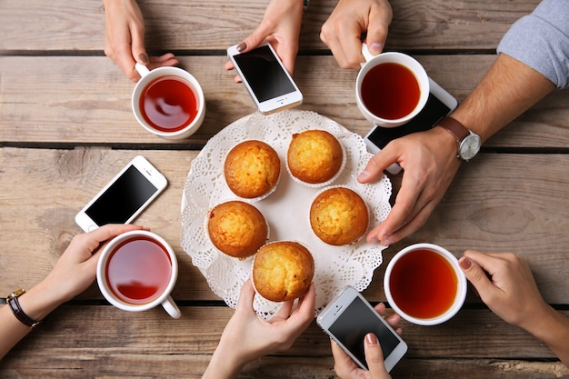 Four hands with smart phones holding  cups with tea, on wooden table