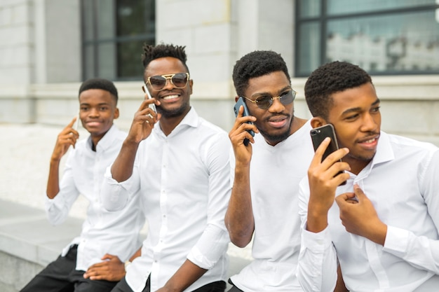 Четыре красивых молодых африканца в белых рубашках с телефонами в руках