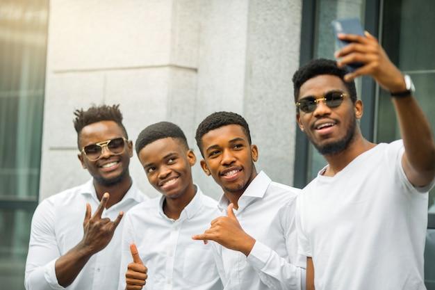 Четверо красивых молодых африканских мужчин в белых рубашках
