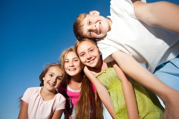 Четыре счастливых красивых ребенка, глядя на камеру сверху в солнечный летний день и голубое небо. смотрит в камеру с забавным лицом и зубастой улыбкой. вид снизу.