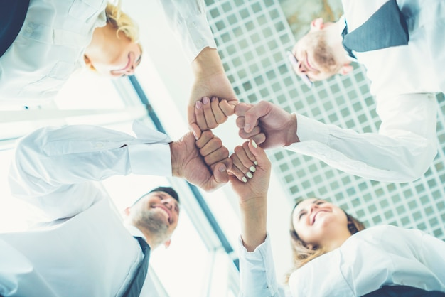 The four happy business people greeting with a fist