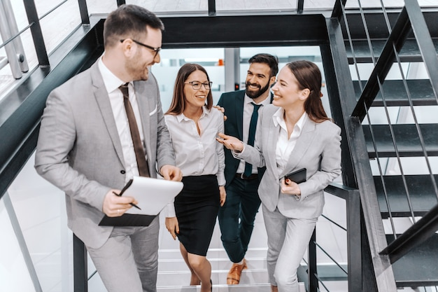 Четыре счастливых коллеги в официальной одежде поднимаются по лестнице и разговаривают о делах. концепция корпоративного бизнеса.